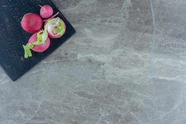Een uitstalling van radijsjes op de snijplank op de marmeren tafel.