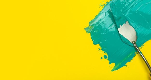 Een uitstrijkje van turquoise verf op een schone gele achtergrond. uitgesmeerd uitgesmeerde verftextuur en tekengereedschappen. kopieer ruimte