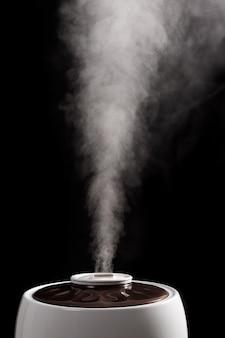 Een ultrasone luchtbevochtiger op een zwarte achtergrond