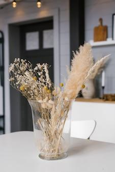 Een vaas met gedroogde bloemen op tafel. scandinavische klassieke kamer met houten en witte details, minimalistisch interieur. gezellig huis.
