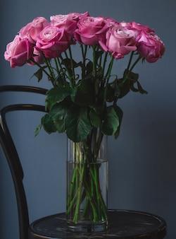 Een vaas met water en roze rozen erin
