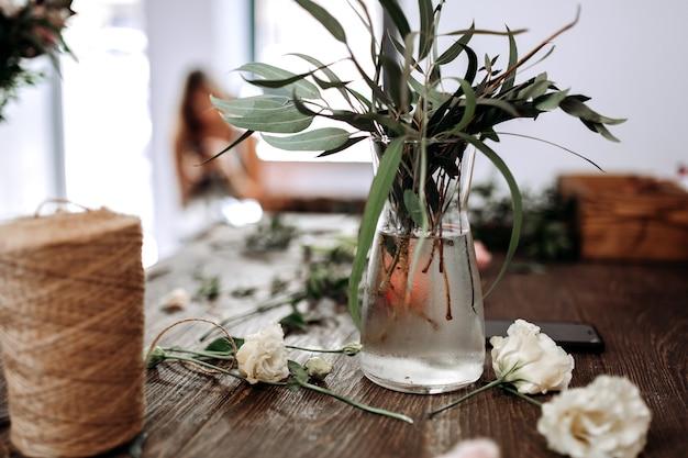 Een vaas met water en takken met groene bladeren en klos touw op de tafel van bloemist