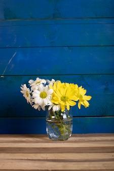 Een vaas met witte en gele bloemen