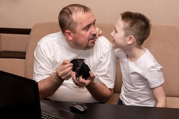 Een vader aan een zwarte tafel met een laptop laat zijn zoon een lege portemonnee zien