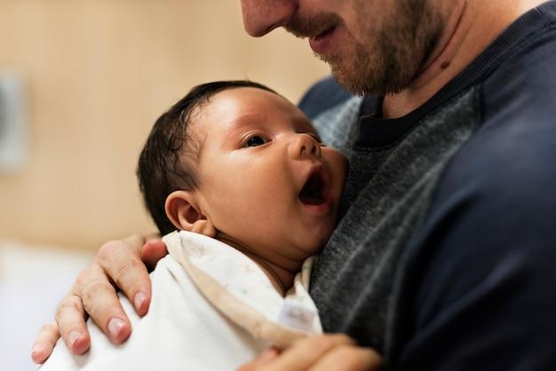 Een vader die een pasgeboren baby draagt