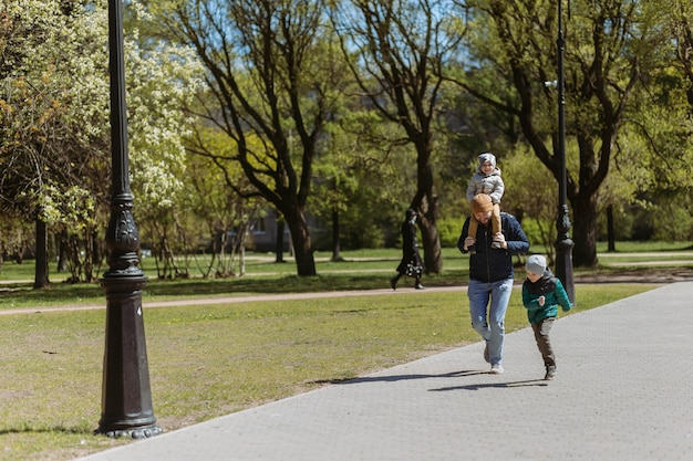 Een vader die met zijn twee zonen door de straat rent. tijd doorbrengen met kinderen in de frisse lucht in de herfst. sint-petersburg, rusland