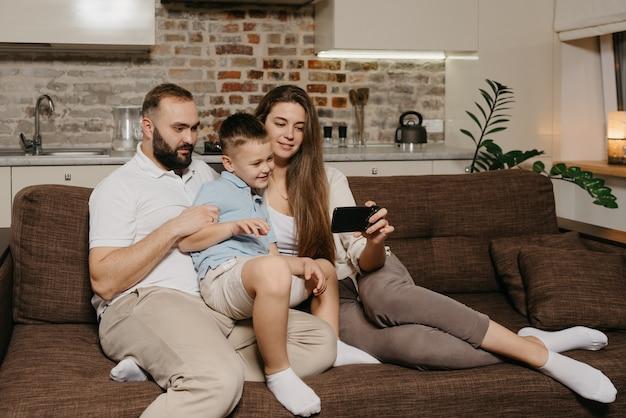 Een vader, een zoon en een jonge moeder kijken naar een video op een smartphone op de bank