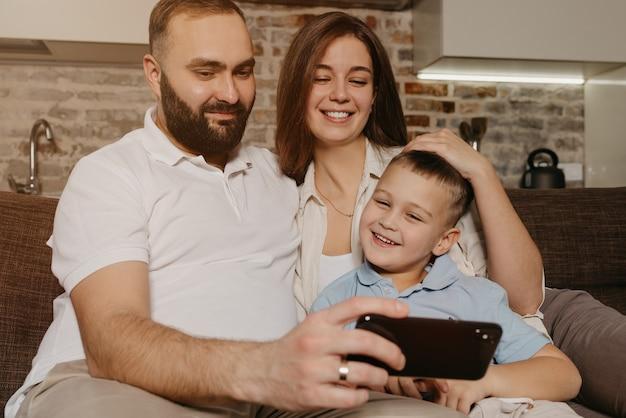 Een vader, een zoon en een moeder kijken naar video op de bank
