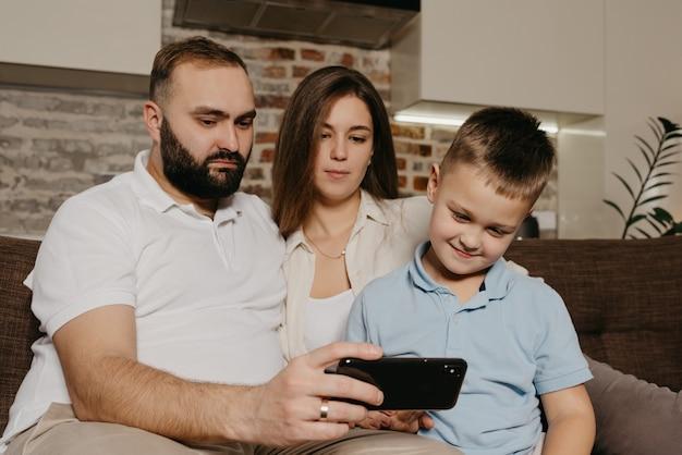 Een vader, een zoon en een moeder kijken video op de bank. een sombere echtgenoot met een baard demonstreert de show 's avonds op de smartphone aan een kind en een vrouw thuis.