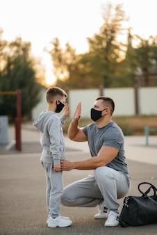 Een vader en kind staan in maskers op een sportveld na een training tijdens zonsondergang