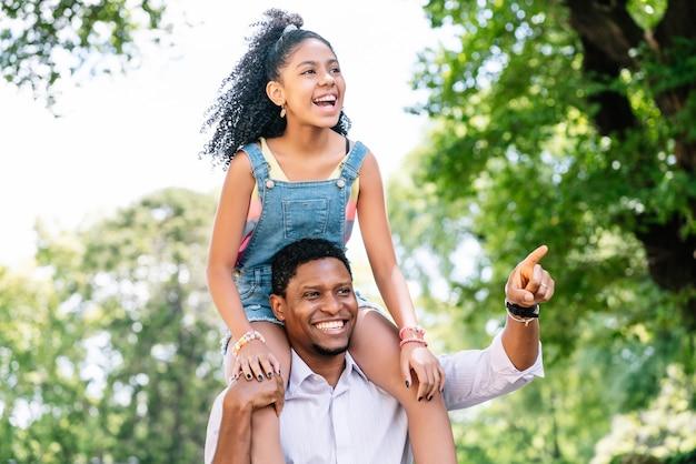 Een vader en zijn dochter hebben plezier en brengen veel tijd samen door terwijl ze buiten op straat wandelen.