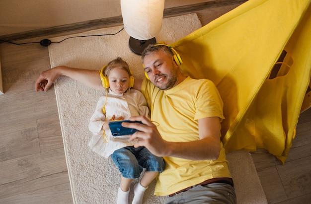 Een vader en zijn mooie dochtertje liggen in gele koptelefoon op de vloer en luisteren naar muziek aan de telefoon.