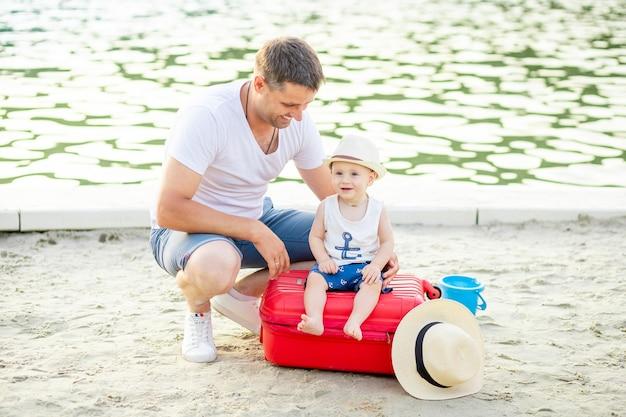 Een vader en zijn zoontje zitten op een rode koffer op een zanderige dijk aan zee, het concept van reizen en recreatie