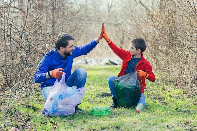 Een vader en zoon maken het vuilnispark schoon vrijwilligers maken het bos schoon van plastic flessen en brengen samen tijd door terwijl ze zich verheugen over het verrichte werk en de voordelen voor het milieu