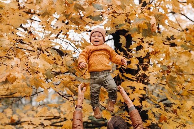 Een vader gooit een kind tegen de achtergrond van herfstbladeren in het park. vader gooit zijn zoon op de herfstbladeren.