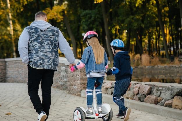 Een vader helpt en leert zijn jonge kinderen om tijdens zonsondergang op een segway in het park te rijden. familievakantie in het park.