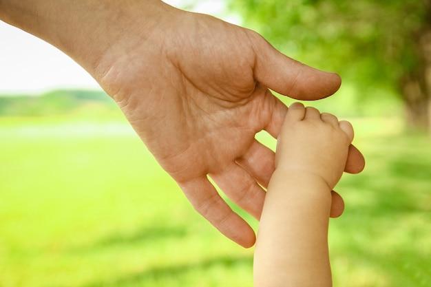 Een vader houdt de hand van een klein kind in het park op de achtergrond van de natuurvakantie