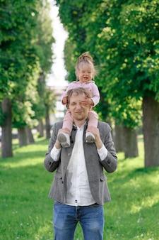 Een vader houdt zijn dochtertje op zijn schouders