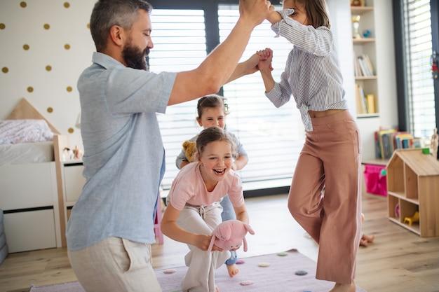 Een vader met drie dochters binnenshuis, spelend op de vloer. Premium Foto