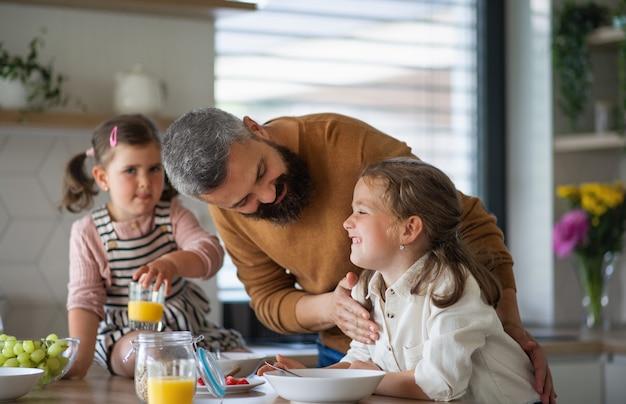 Een vader met drie dochters die binnen thuis ontbijten in de keuken