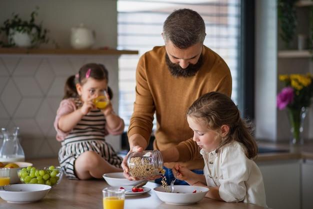 Een vader met drie dochters die binnenshuis thuis ontbijten in de keuken.