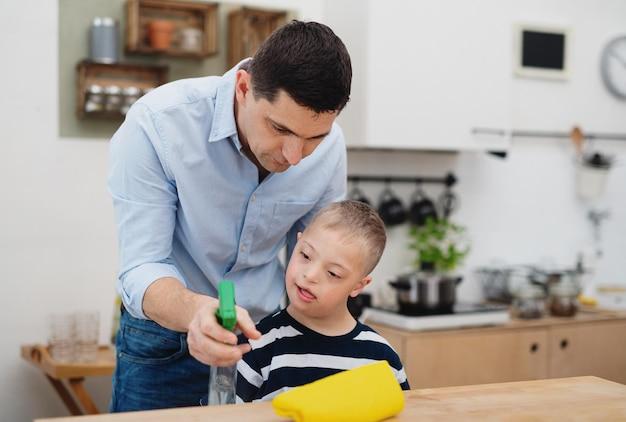 Een vader met een gelukkige zoon met het syndroom van down binnenshuis in de keuken, schoonmaaktafel.