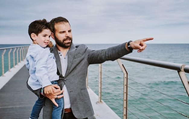 Een vader met zijn zoon op een bewolkte dag geeft iets aan