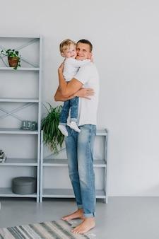 Een vader van een man knuffelt stevig met zijn zoon in zijn armen houdt hem vast. gekleed in jeans en witte t-shirts in een licht interieur.