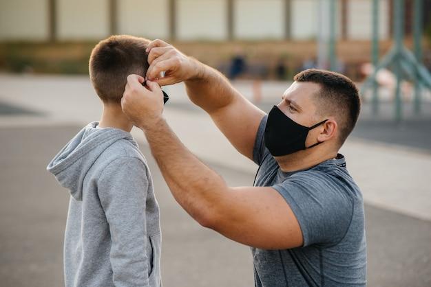 Een vader zet een masker op zijn zoon op de speelplaats na een training tijdens zonsondergang.