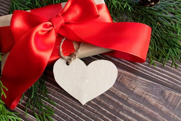Een vakantiepakket met een rode strik en een hartvormig label voor tekst.