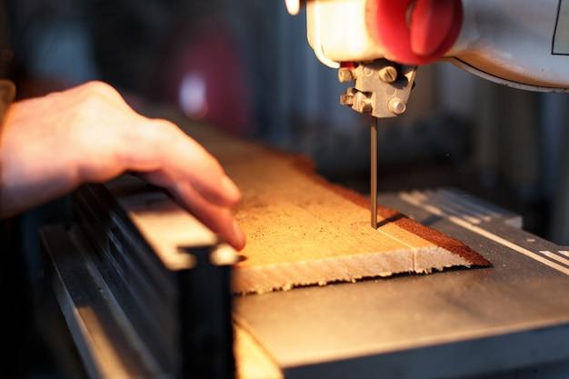 Een vakman die een plank van hout met lintzaag snijdt