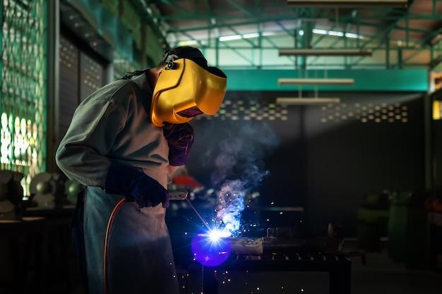 Een vakman is aan het lassen met werkstukstaal. werkende persoon over lasserstaal gebruik van elektrische lasmachine er komen lichtlijnen uit en veiligheidsuitrusting in de fabrieksindustrie.
