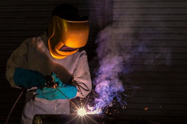 Een vakman is aan het lassen met werkstukstaal. werknemer over lasserstaal elektrisch lasapparaat gebruiken er komen lichtlijnen naar buiten en veiligheidsuitrusting in de fabrieksindustrie.