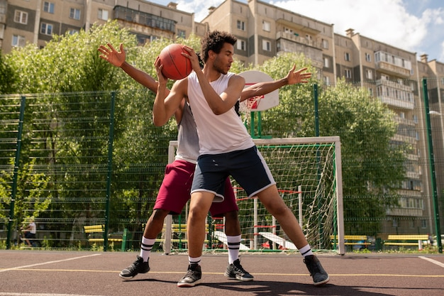 Een van de basketbalspelers met een bal die probeert zijn rivaal het niet weg te laten nemen tijdens een buitenspel