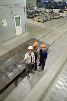 Een van de drie jonge ingenieurs in uniform en hardhats die naar een nieuwe enorme industriële machine wijst terwijl ze deze aan collega's laat zien