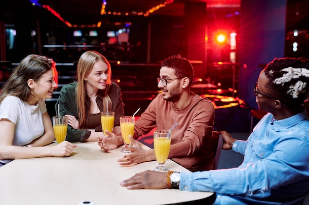 Een van de jonge, aanhankelijke interculturele vrienden die iets uitlegt terwijl anderen hem aan tafel in het café van het recreatiecentrum bekijken