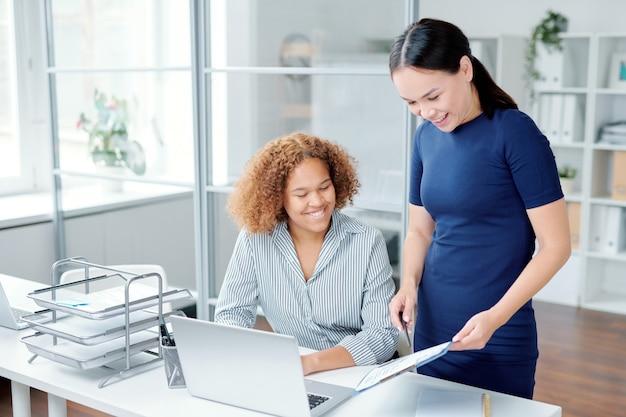 Een van de jonge vrouwelijke managers die op financieel papier wijzen
