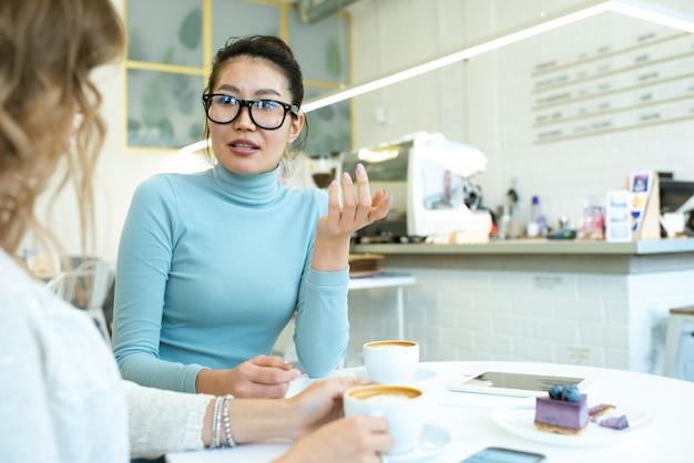 Een van de jonge vrouwen die haar vriend iets per kopje cappuccino uitlegt tijdens een gesprek aan de tafel in het café