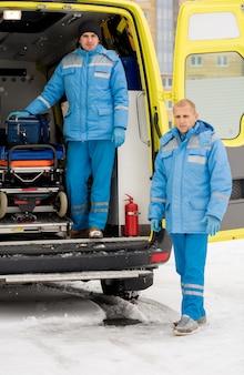 Een van de mannelijke paramedici in uniform gaat een brancard nemen terwijl zijn collega bij de ambulanceauto staat