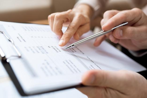 Een van de mensen houdt een pen boven papier terwijl hij de financiële uitgaven en andere punten van het document bespreekt