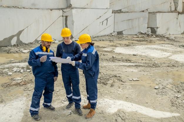 Een van de moderne bouwers die tijdens teamwerk naar de schets van de constructie wijst