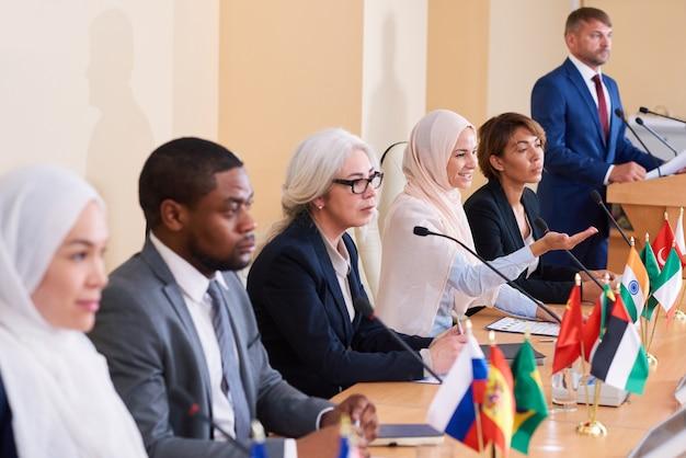 Een van de moslimvrouwen in traditionele hijab legt haar standpunt uit aan een buitenlandse afgevaardigde op een zakenconferentie