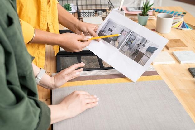 Een van de twee jonge creatieve vrouwelijke ontwerpers die op de foto van het interieur van de kamer op papier wijzen terwijl ze deze bespreken met een collega in de studio