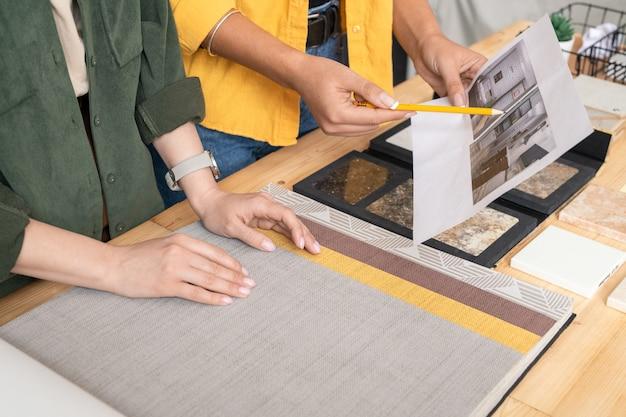 Een van de twee jonge vrouwelijke ontwerpers van interieur wijzend op papier met foto van appartement