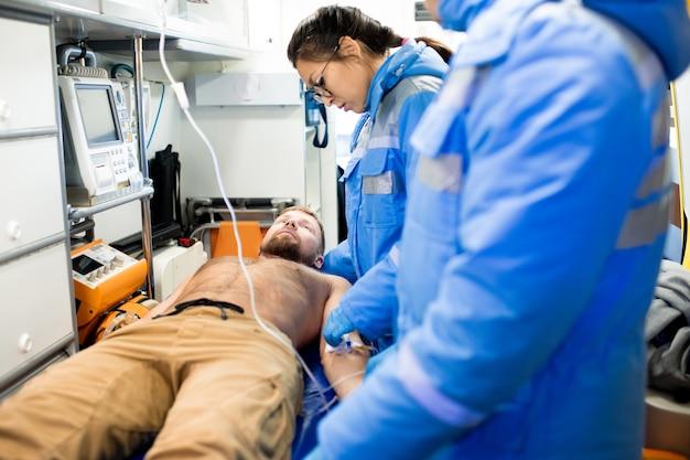 Een van de twee paramedici in uniform die eerste hulp verleent aan zieke shirtless man op brancard met collega in de buurt