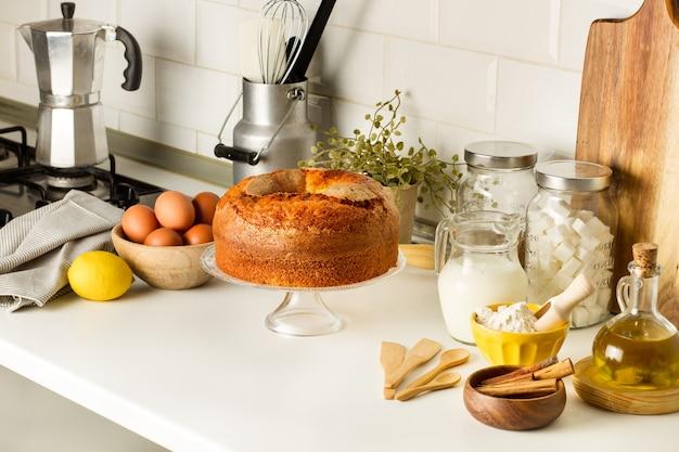 Een vanillecake en ingrediënten op een caketribune op het aanrecht in de keuken