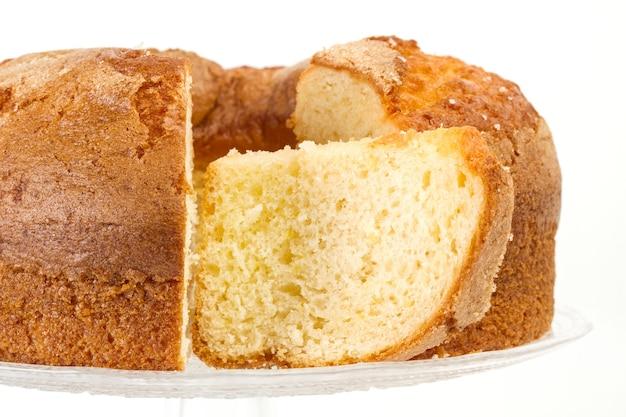 Een vanillecake en stukken op een tribune van de kristalcake en geïsoleerd op een witte achtergrond