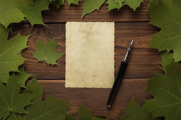 Een vel antiek papier en een vulpen in een frame van esdoornbladeren op een houten ondergrond. herfst stemming. correspondentie.