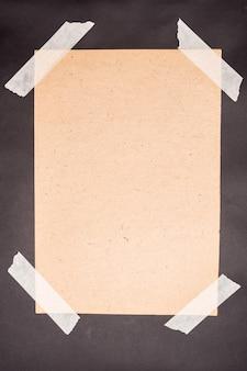Een vel kraftpapier gelijmd met wit plakband op een zwarte achtergrond