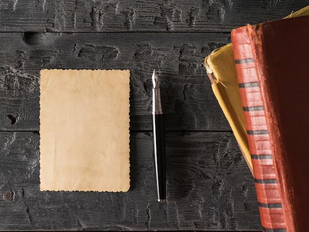 Een vel oud papier en een vulpen met boeken op een houten tafel. retro schrijfpapier. plat leggen het uitzicht vanaf de top.